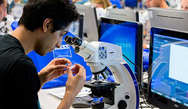 Male student looking at a slide with a microscope and computer